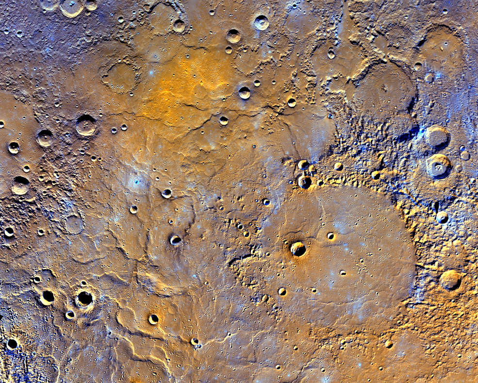 A view of Mercury's northern volcanic plains is shown in enhanced color to emphasize different types of rocks on Mercury's surface. In the bottom right portion of the image, the 181-mile- (291-kilometer)-diameter Mendelssohn impact basin, named after the German composer, appears to have been once nearly filled with lava. Toward the bottom left portion of the image, large wrinkle ridges, formed during lava cooling, are visible. Also in this region, the circular rims of impact craters buried by the lava can be identified. Near the top of the image, the bright orange region shows the location of a volcanic vent. - Image Credits: NASA/JHUAPL/Carnegie Institution of Washington