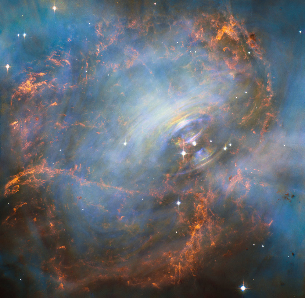 While many other images of the famous Crab Nebula have focused on the filaments in the outer part of the nebula, this image shows the very heart of the Crab Nebula including the central neutron star — it is the rightmost of the two bright stars near the centre of this image. The rapid motion of the material nearest to the central star is revealed by the subtle rainbow of colours in this time-lapse image, the rainbow effect being due to the movement of material over the time between one image and another. – Image Credit: NASA, ESA