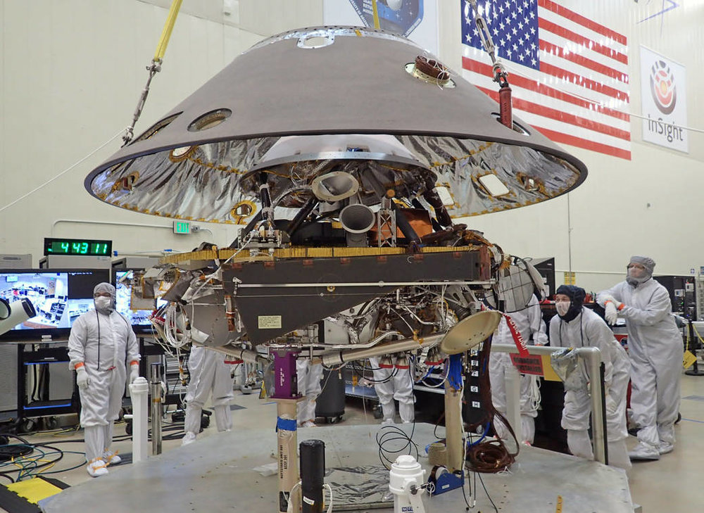 Back shell of NASA's InSight spacecraft is being lowered onto the mission's lander, which is folded into its stowed configuration. The back shell and a heat shield form the aeroshell, which will protect the lander as the spacecraft plunges into the upper atmosphere of Mars. Launch now rescheduled to May 2018 to fix French-built seismometer. - Image Credit: NASA/JPL-Caltech/Lockheed Martin