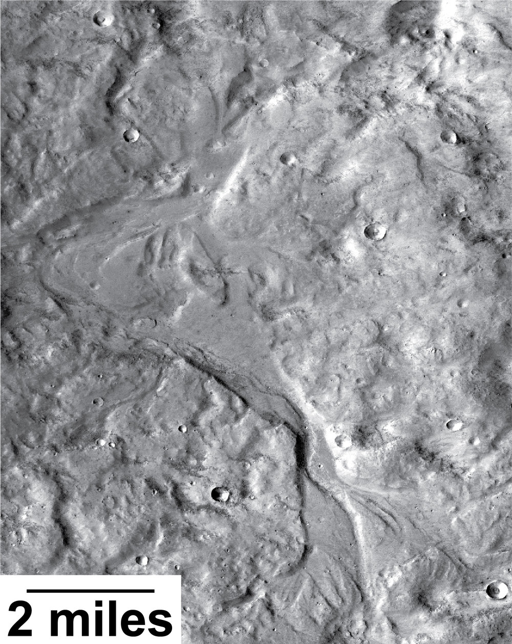 Streamlined forms in this Martian valley resulted from the outflow of a lake hundreds of millions years more recently than an era of Martian lakes previously confirmed. This image from the Context Camera on NASA's Mars Reconnaissance Orbiter covers an area in Arabia Terra about 8 miles wide. - Image   Credits: NASA/JPL-Caltech/MSSS