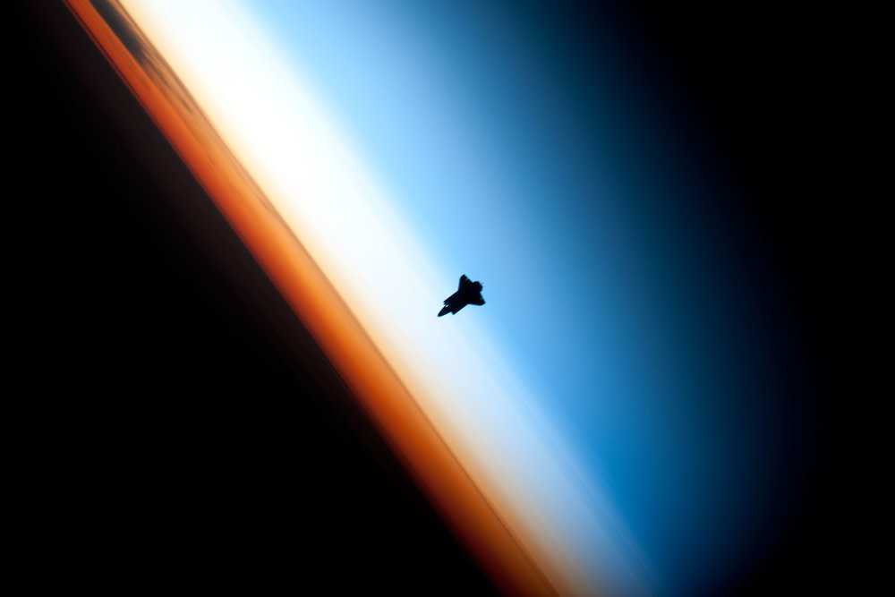 Space Shuttle Endeavor silhouetted against Earth's atmosphere. The orange layer is the troposphere, the white layer is the stratosphere and the blue layer the mesosphere. - Image Credit: NASA