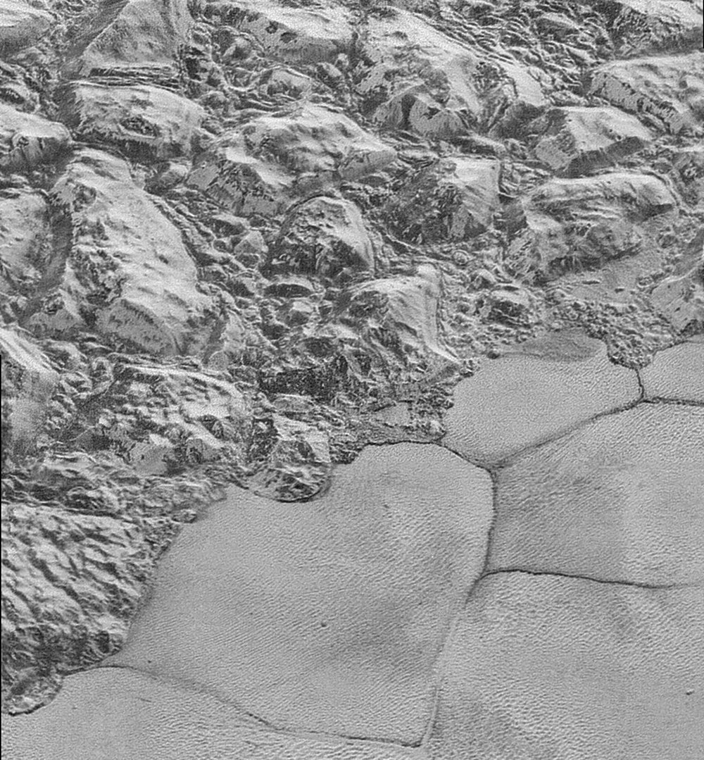 The Mountainous Shoreline of Sputnik Planum on Pluto. Great blocks of Pluto's water-ice crust appear jammed together in the informally named al-Idrisi mountains. Some mountain sides appear coated in dark material, while other sides are bright. - Image Credit: NASA/Johns Hopkins University Applied Physics Laboratory/Southwest Research Institute.