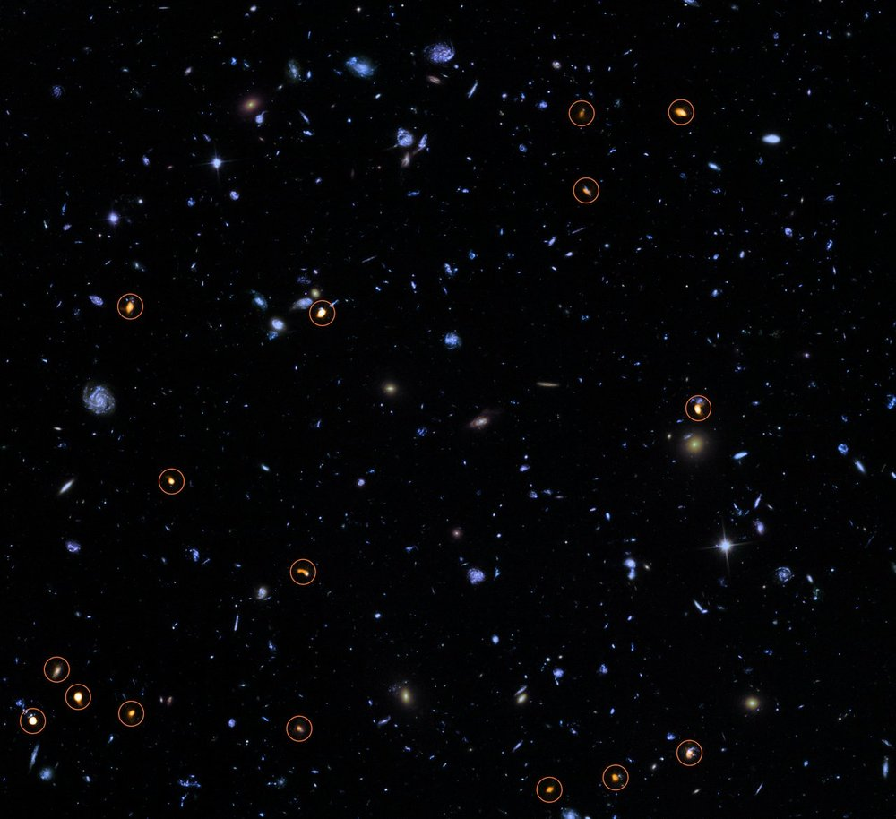 This image combines a background picture taken by the NASA/ESA Hubble Space Telescope (blue/green) with a new very deep ALMA view of this field (orange, marked with circles). All the objects that ALMA sees appear to be massive star-forming galaxies  . - Image Credit: ALMA (ESO/NAOJ/NRAO)/NASA/ESA/J. Dunlop et al. and S. Beckwith (   STScI   ) and the HUDF Team.