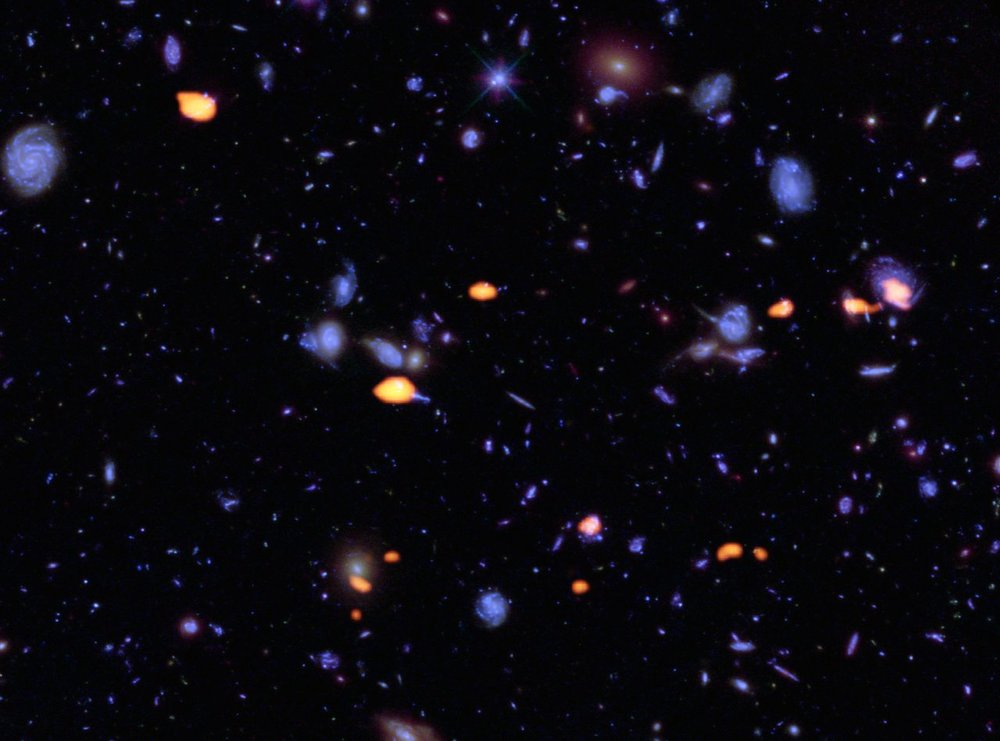 A trove of galaxies, rich in carbon monoxide (indicating star-forming potential) were imaged by ALMA (orange) in the Hubble Ultra Deep Field. The blue features are galaxies imaged by Hubble. This image is based on the very deep ALMA survey by Manuel Aravena, Fabian Walter and colleagues, covering about one sixth of the full HUDF area. – image Credit: B. Saxton (NRAO/AUI/NSF); ALMA (ESO/NAOJ/NRAO); NASA/ESA Hubble