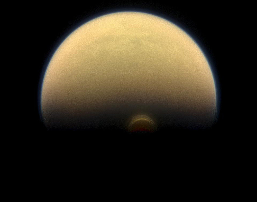 Slipping into shadow, the south polar vortex at Saturn's moon Titan still stands out against the orange and blue haze layers that are characteristic of Titan's atmosphere. Images like this, from NASA's Cassini spacecraft, lead scientists to conclude that the polar vortex clouds form at a much higher altitude -- where sunlight can still reach -- than the lower-altitude surrounding haze. – Image Credits: NASA/JPL-Caltech/Space Science Institute