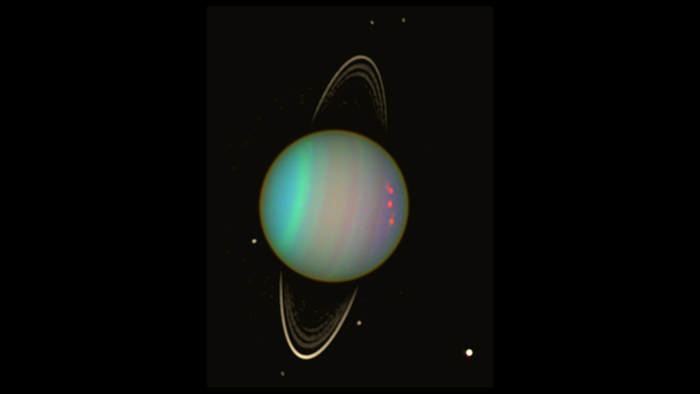 Uranus is seen in this false-color view from NASA's Hubble Space Telescope from August 2003. The brightness of the planet's faint rings and dark moons has been enhanced for visibility. – Image Credits: NASA/Erich Karkoschka (Univ. Arizona)