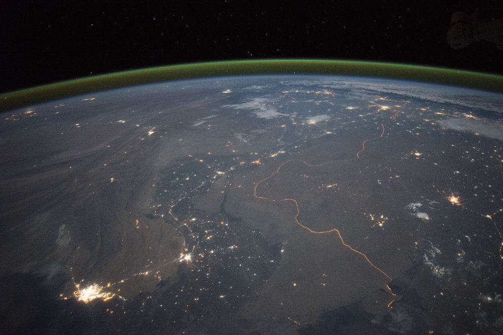 Nighttime panorama showing Pakistan's Indus River valley, taken from space. The green band above the horizon is airglow. – Image Credit:   NASA Earth Observatory