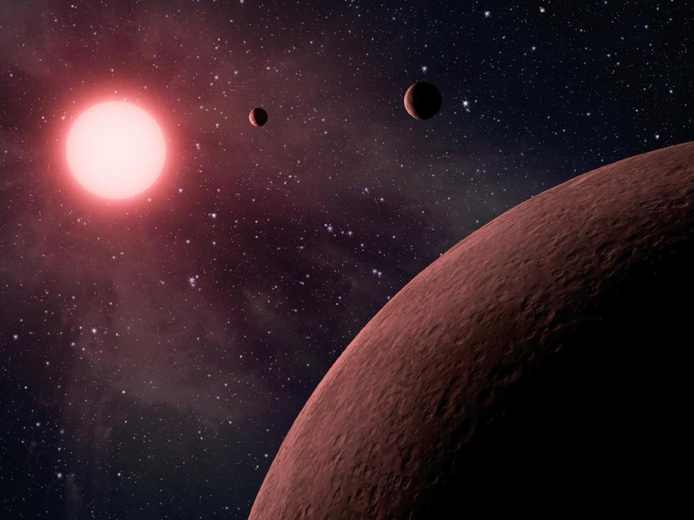 Artist's impression of a system of exoplanets orbiting a low mass, red dwarf star. - Image Credit: NASA/JPL