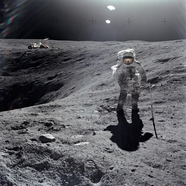 Sample collection on the surface of the Moon. Apollo 16 astronaut Charles M. Duke Jr. is shown collecting samples with the Lunar Roving Vehicle in the left background - Image Credit: NASA