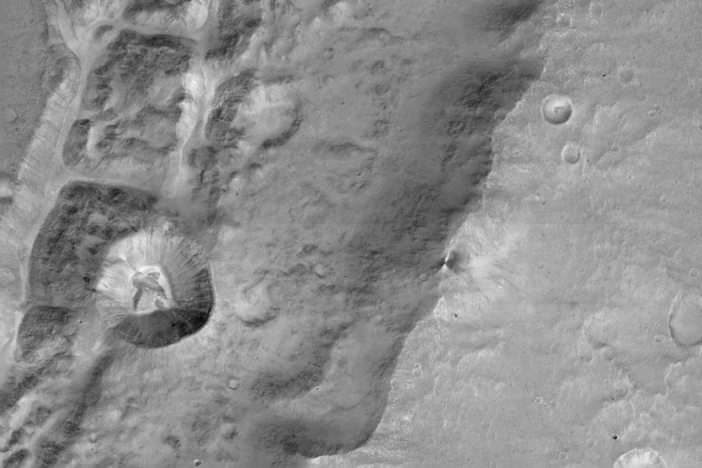 One of the first images from the Mars Camera, CaSSIS, on the ExoMars Trace Gas Orbiter. The image shows a 1.4 km sized crater (left center) on the rim of a much larger crater near the Mars equator. Credit: ESA/Roscosmos/ExoMars/CaSSIS/UniBE.