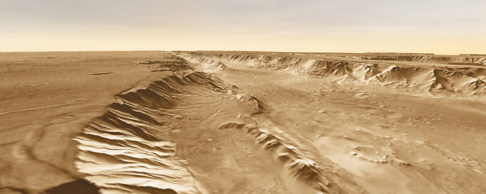 A small basin (center foreground) lies below the southern rim of Melas Chasma, part of Valles Marineris. This is one of the eight potential landing sites being studied for the Mars 2020 rover. – Image Credits: NASA/JPL-Caltech/Arizona State University, R. Luk