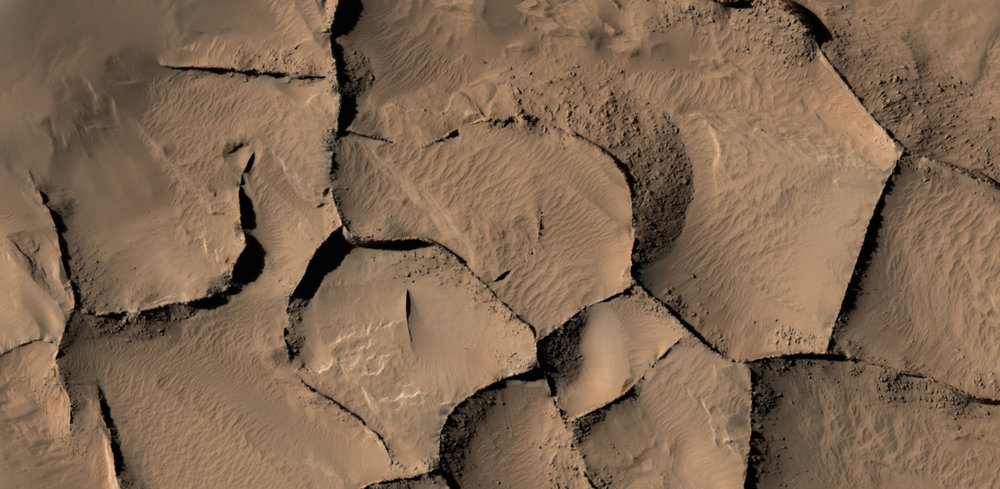 This view from the HiRISE camera on NASA's Mars Reconnaissance Orbiter shows part of an area on Mars where narrow rock ridges, some as tall as a 16-story building, intersect at angles forming corners of polygons. – Image Credits: NASA/JPL-Caltech/Univ. of Arizona