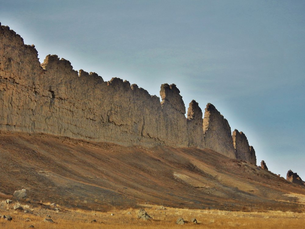 This photograph from Shiprock in northwestern New Mexico shows a ridge roughly 30 feet (about 10 meters) tall that formed from lava filling an underground fracture then resisting erosion better than the material around it did. - Image   Credits: NASA/JPL-Caltech
