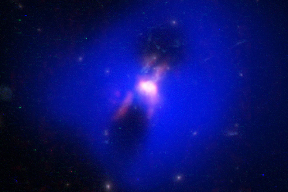 "This composite image shows powerful radio jets from the supermassive black hole at the center of a galaxy in the Phoenix Cluster inflating huge ""bubbles"" in the hot, ionized gas surrounding the galaxy. The cavities inside the blue region were imaged by NASA's Chandra X-ray observatory. Hugging the outside of these bubbles, ALMA discovered an unexpected trove of cold gas, the fuel for star formation (red). The background image is from the Hubble Space Telescope. - Image Credit: ALMA (ESO/NAOJ/NRAO) H.Russell, et al.; NASA/ESA Hubble; NASA/CXC/MIT/M.McDonald et al.; B. Saxton (NRAO/AUI/NSF)"