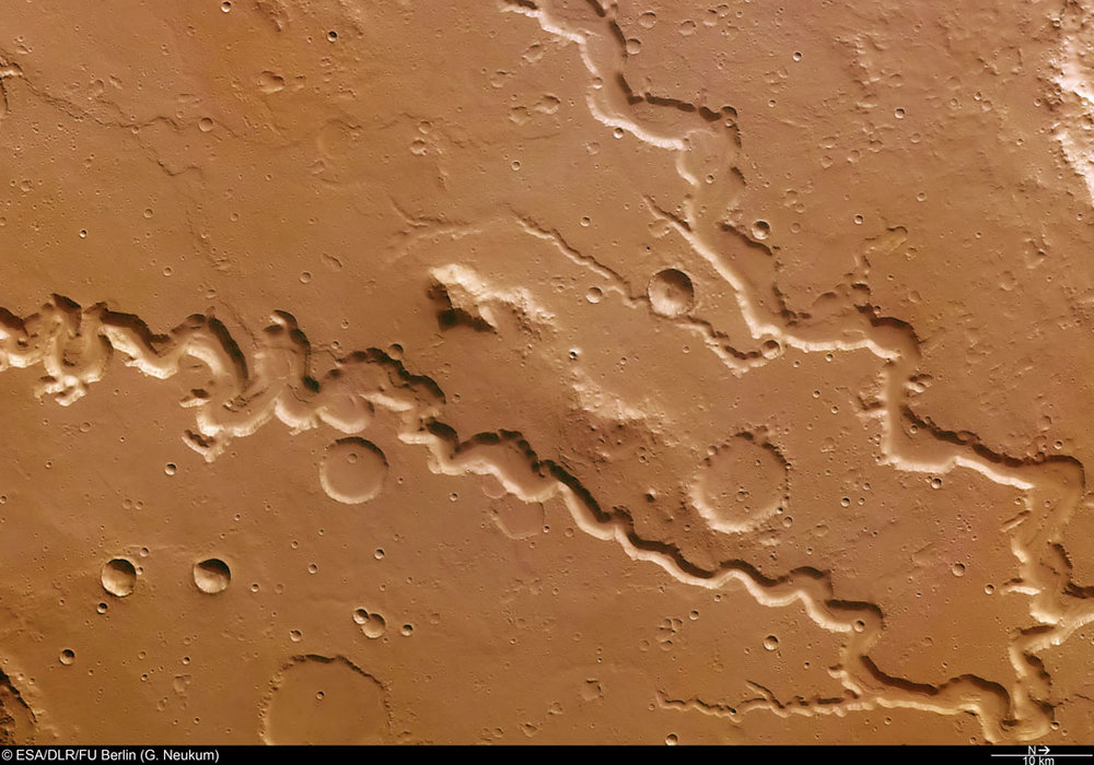 Water, water everywhere … once upon a time. Nanedi Valles, a roughly 500-mile-long (800 km) valley extending southwest-northeast and photographed by Mars Express. In this view, Nanedi Valles ranges from approximately 0.5 – 3 miles (0.8- to 5.0 km) wide and extends to a maximum of about 1,640 feet (500 meters) below the surrounding plains. The valley's origins remain unclear, with scientists debating whether erosion caused by ground-water outflow, flow of liquid beneath an ice cover or collapse of the surface in association with liquid flow is responsible. In all cases, it's clear that water was involved. - Image Credit: ESA/DLR/FU Berlin (G. Neukum)