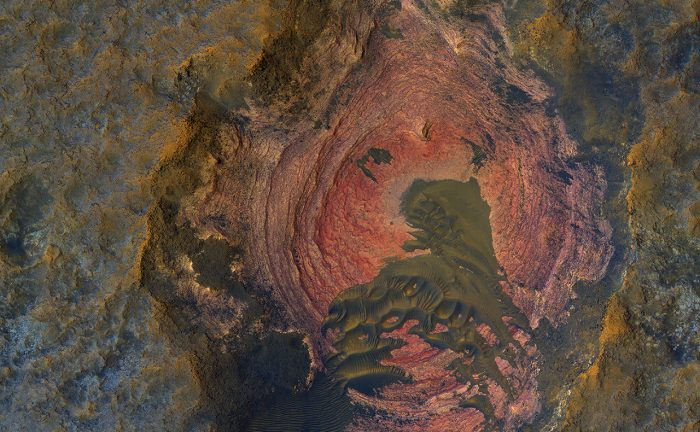 This colorful image of Martian bedrock, punctuated in the center by dunes, is courtesy of the HiRise camera aboard NASA's Mars Reconnaissance Orbiter. - Image Credit: NASA/JPL/University of Arizona