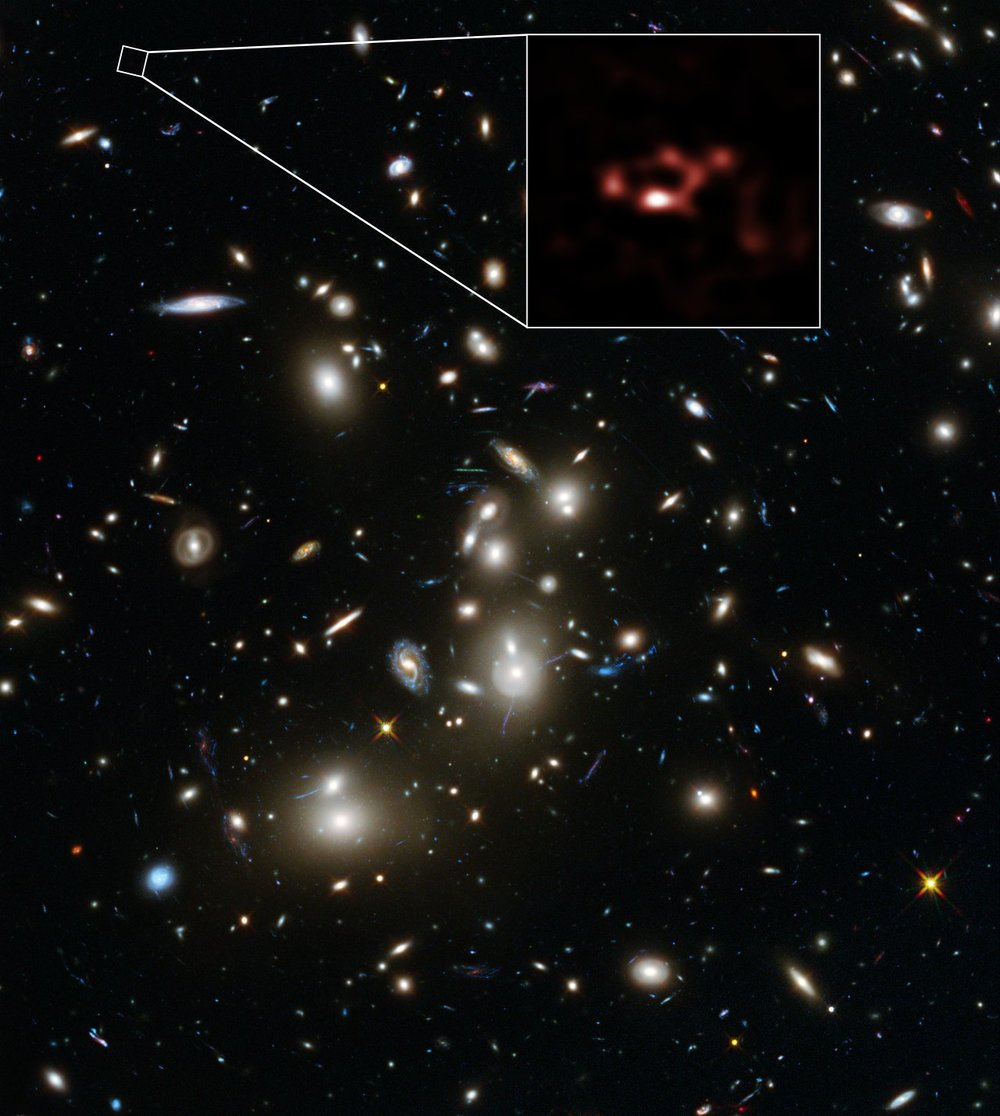This image is dominated by a spectacular view of the rich galaxy cluster Abell 2744 from the NASA/ESA Hubble Space Telescope. But, far beyond this cluster, and seen when the Universe was only about 600 million years old, is a very faint galaxy called A2744_YD4. New observations of this galaxy with ALMA, shown in red, have demonstrated that it is rich in dust. - Image Credit: ALMA (ESO/NAOJ/NRAO), NASA, ESA, ESO and D. Coe (STScI)/J. Merten (Heidelberg/Bologna)