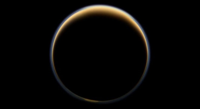 ASA's Cassini spacecraft looks toward the night side of Saturn's largest moon and sees sunlight scattering through the periphery of Titan's atmosphere and forming a ring of color. - Image Credit: NASA/JPL-Caltech/Space Science Institute