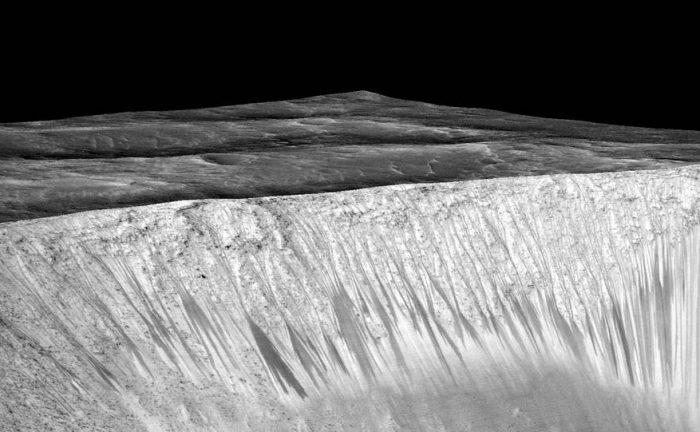 These dark streaks, called recurring slope lineae (RSL), are on the sloped wall of a crater on Mars. A new study says they may have been formed by boiling water. - Image Credit: NASA/JPL-Caltech/Univ. of Arizona