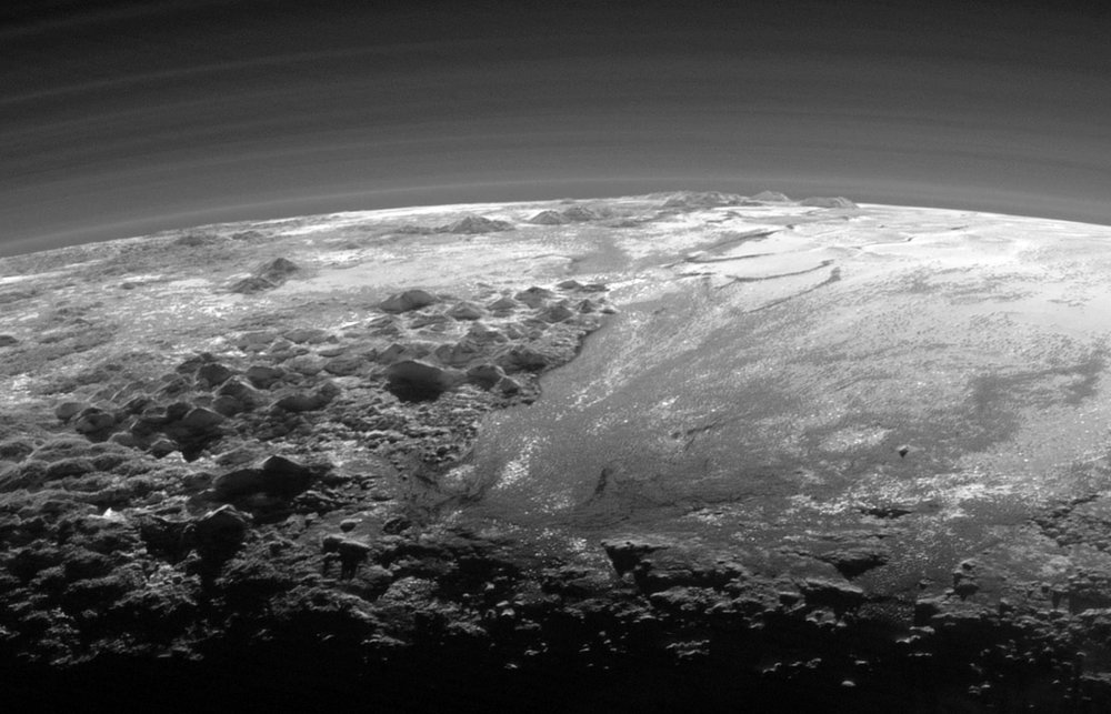 Haze with multiple layers in the atmosphere of Pluto. Part of the plain Sputnik Planitia with nearby mountains is seen below. Photo by New Horizons, taken 15 min after the closest approach to Pluto. - Image Credit: NASA/JHUAPL/SwRI