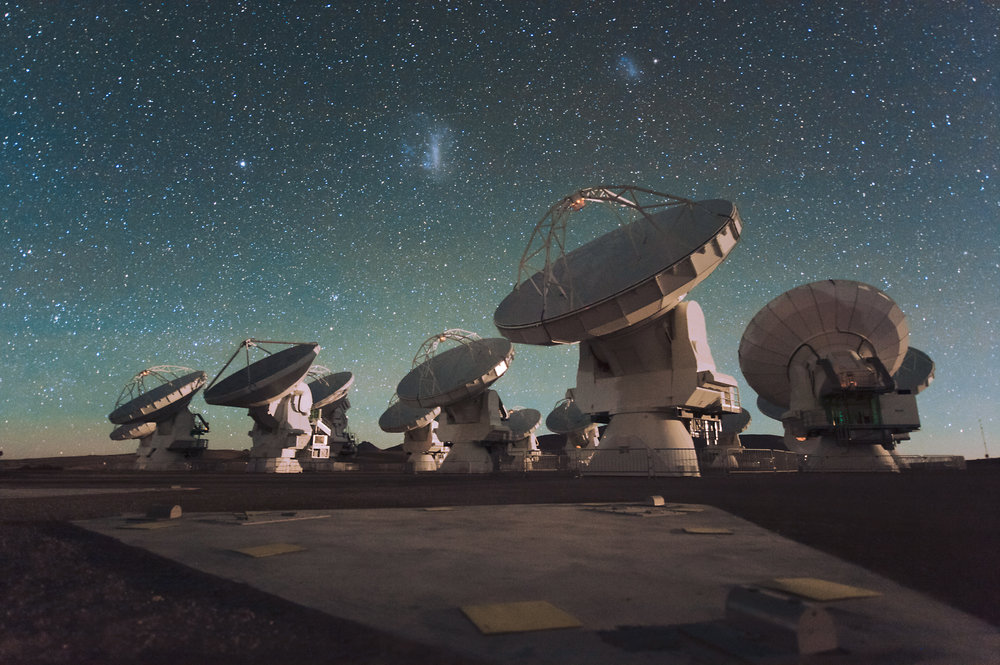 Antennas of the Atacama Large Millimeter/submillimeter Array (ALMA), on the Chajnantor Plateau in the Chilean Andes. The Large and Small Magellanic Clouds, two companion galaxies to our own Milky Way galaxy, can be seen as bright smudges in the night sky, in the centre of the photograph. - Image Credit: ESO/C. MAlin