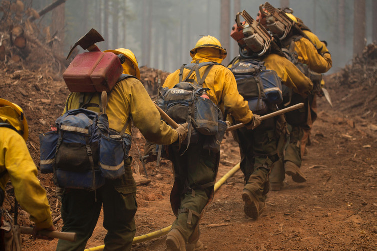 Hotshot crews head out to fight the Happy Camp Complex fire in California's Klamath National Forest in 2014. The fire was started by lightning strikes and burned 134,000 acres. - Image Credit:  Kari Greer, US Forest Service/Flickr ,  CC BY