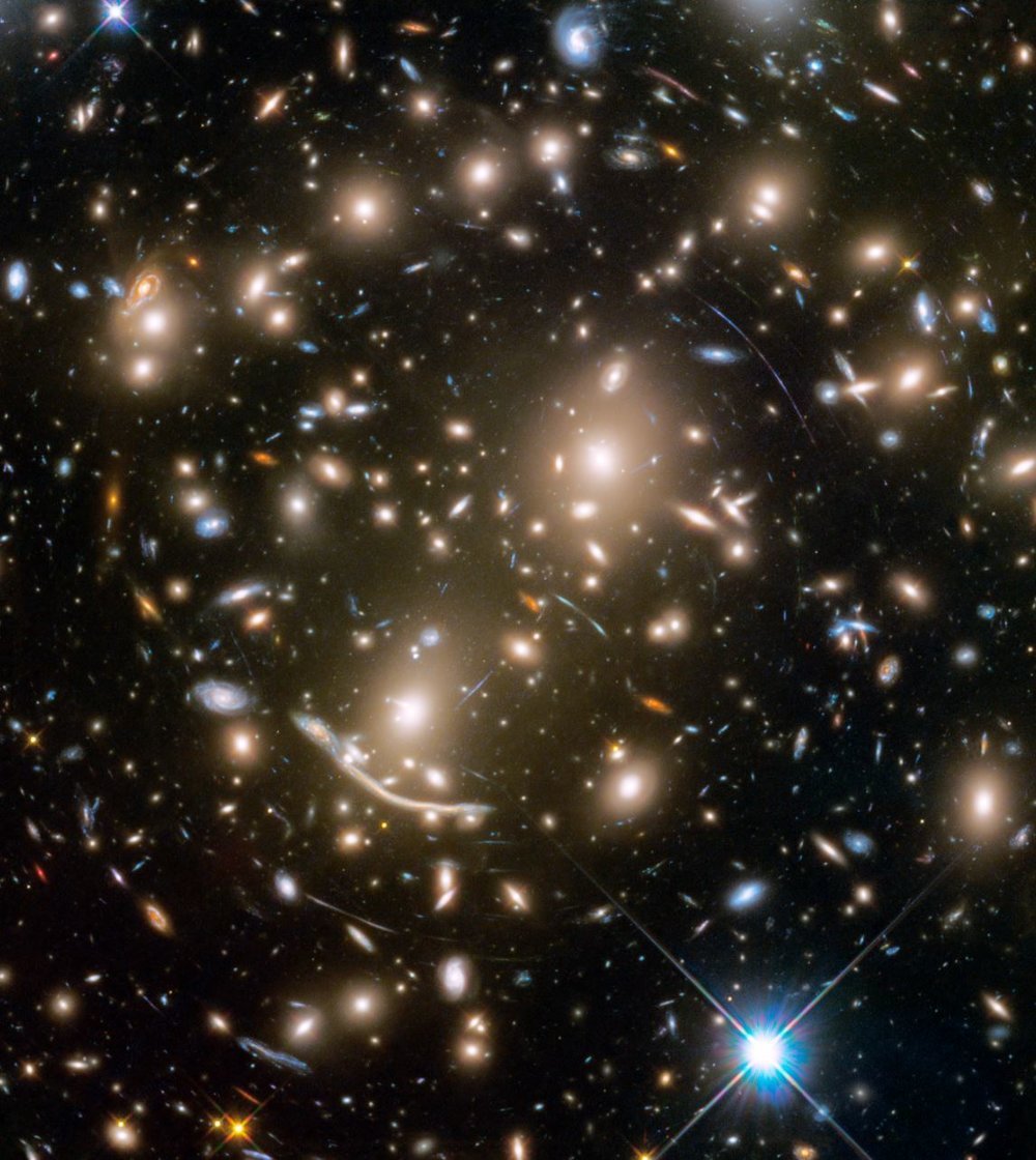 Galaxy cluster Abell 370 contains several hundred galaxies tied together by the mutual pull of gravity. Photographed in a combination of visible and near-infrared light, the brightest and largest galaxies are the yellow-white, massive, elliptical galaxies containing many hundreds of billions of stars each. Spiral galaxies have younger populations of stars and are bluish. Mysterious-looking arcs of blue light are distorted images of remote galaxies behind the cluster. The cluster acts as a huge lens in space that magnifies and stretches images of background galaxies like a funhouse mirror. - Image Credits: NASA, ESA, and J. Lotz and the HFF Team (STScI) - (click to enlarge)
