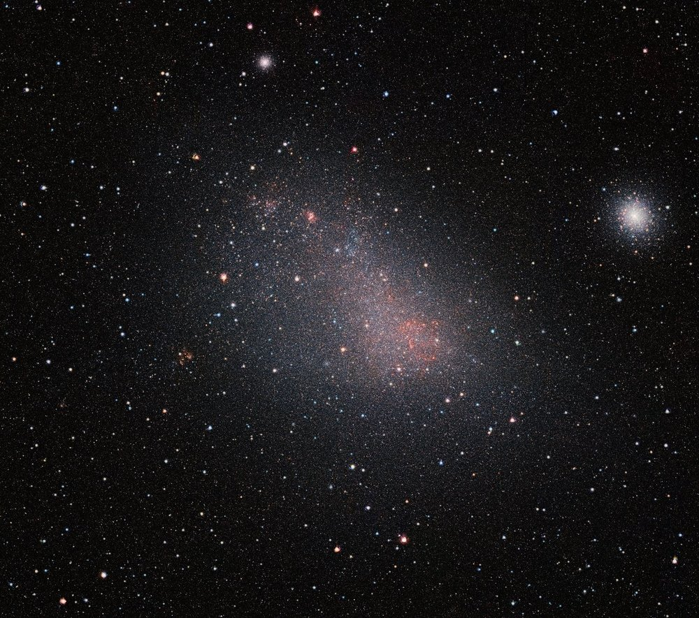 The Small Magellanic Cloud (SMC) galaxy is a striking feature of the southern sky even to the unaided eye. But visible-light telescopes cannot get a really clear view of what is in the galaxy because of obscuring clouds of interstellar dust. VISTA's infrared capabilities have now allowed astronomers to see the myriad of stars in this neighbouring galaxy much more clearly than ever before. The result is this record-breaking image — the biggest infrared image ever taken of the Small Magellanic Cloud — with the whole frame filled with millions of stars.  As well as the SMC itself this very wide-field image reveals many background galaxies and several star clusters, including the very bright 47 Tucanae globular cluster at the right of the picture. - Image Credit: ESO/VISTA VMC