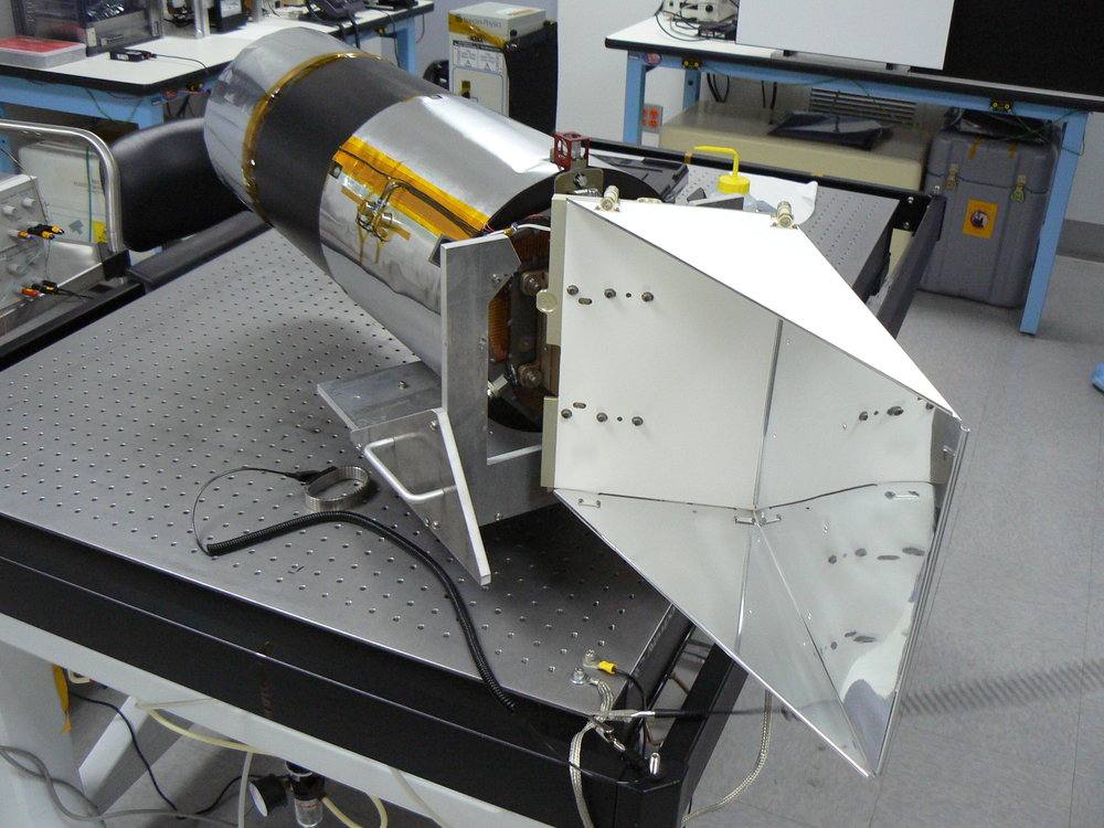 The Narrow Angle Camera sits on a bench in the clean room at Malin Space Science Systems. The radiator (right) extends off the electronics end and keeps the sensor cool while imaging the moon. Computer modeling shows the meteoroid impacted somewhere on the radiator.. - Image Credits: Malin Space Science Systems/Arizona State University