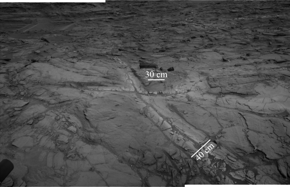 This is a mosaic of images from the navigation cameras on the NASA Curiosity rover shows 'halos' of lighter-toned bedrock around fractures. These halos comprise high concentrations of silica and indicate that liquid groundwater flowed through the rocks in Gale crater longer than previously believed. - Image Credit: NASA/JPL-Caltech.