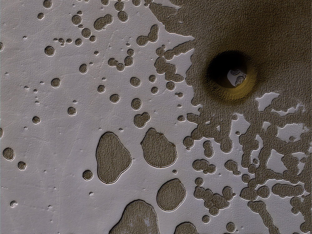 "The HiRISE camera on NASA's Mars Reconnaissance Orbiter captured this unusual crater or pit on the surface of Mars. Frozen carbon dioxide gives the region its unique ""Swiss cheese"" like appearance. - Image Credit: NASA/JPL/University of Arizona"
