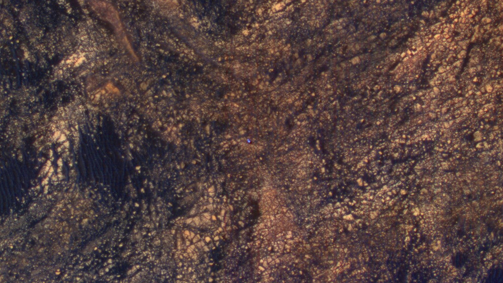 The feature that appears bright blue at the center of this scene is NASA's Curiosity Mars rover amid tan rocks and dark sand on Mount Sharp, as viewed by the HiRISE camera on NASA's Mars Reconnaissance Orbiter on June 5, 2017. The rover is about 10 feet long and not really as blue as it looks here. - Image Credits: NASA/JPL-Caltech/Univ. of Arizona