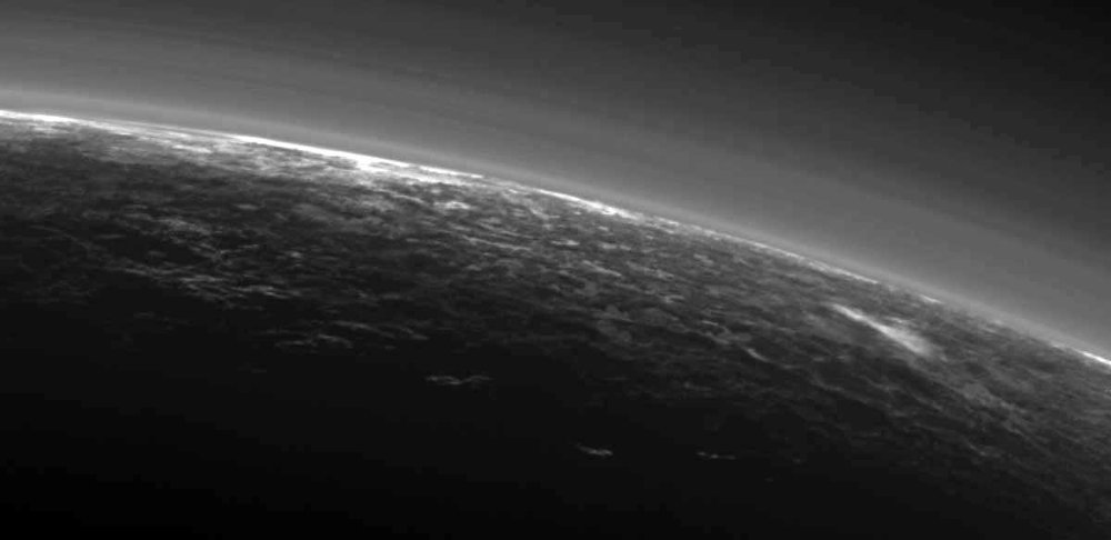 Images sent by NASA's New Horizons spacecraft show possible clouds floating over the frozen landscape including the streaky patch at right. - Image Credit: NASA/JHUAPL/SwR