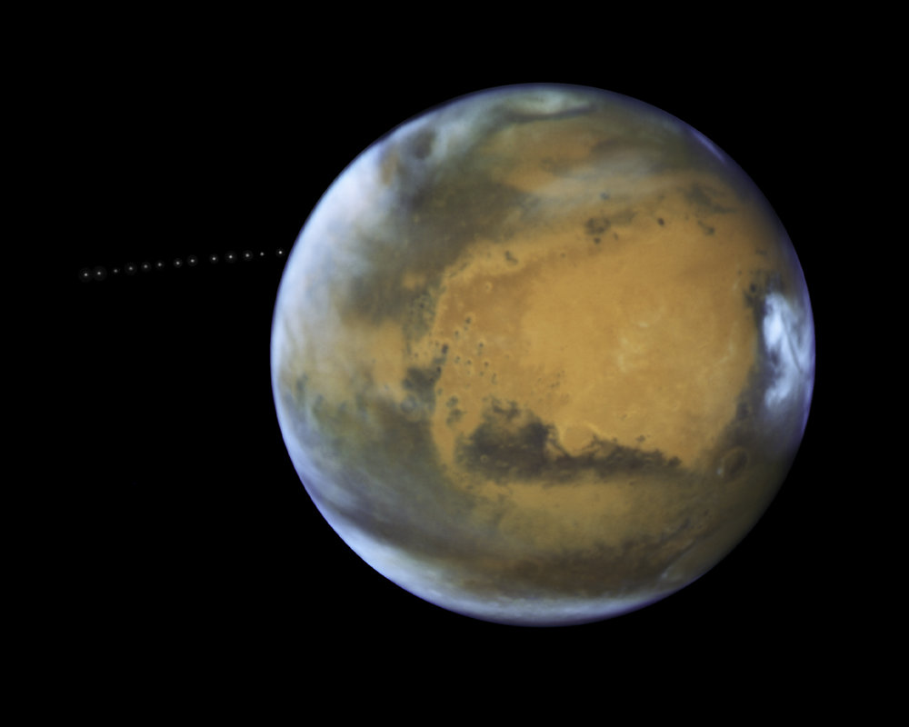 Over the course of 22 minutes, Hubble took 13 separate exposures, allowing astronomers to create a time-lapse image showing the tiny moon Phobos during its orbital trek (white dots) around Mars. This image is a composite of separate exposures acquired by NASA's Hubble WFC3/UVIS instrument.  Banner Animation:  The animation at the top of the page was made from these images. - Image Credits: NASA, ESA, and Z. Levay (STScI), Acknowledgment: J. Bell (ASU) and M. Wolff (Space Science Institute)
