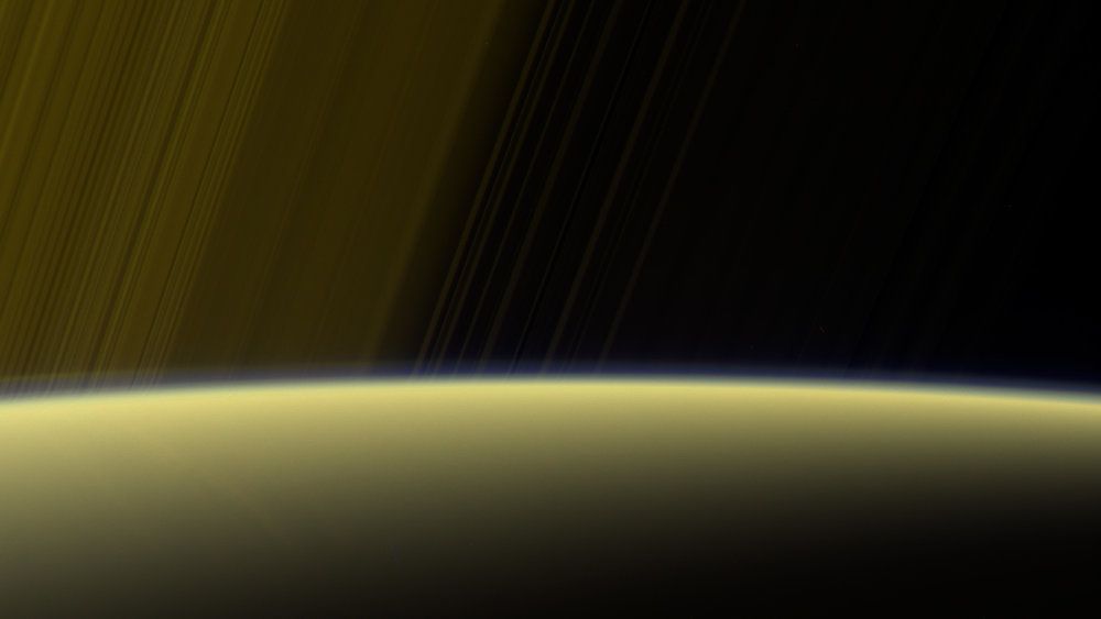 This false-color view from NASA's Cassini spacecraft gazes toward the rings beyond Saturn's sunlit horizon, where a thin haze can be seen along the limb. - Image Credits: NASA/JPL-Caltech/Space Science Institute