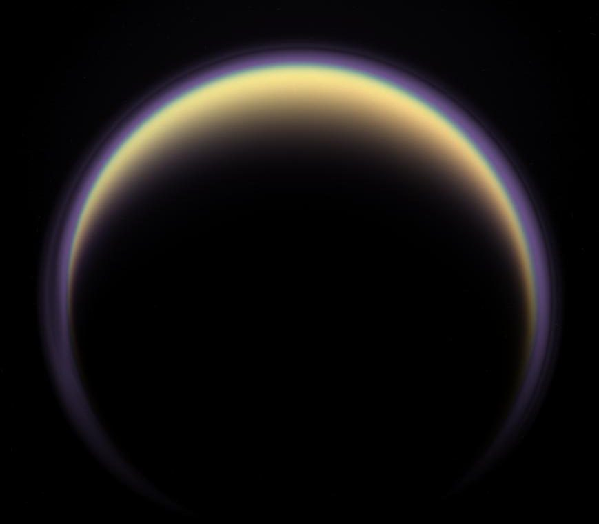 A halo of light surrounds Saturn's moon Titan in this backlit picture, showing its atmosphere. - Image Credit: NASA/JPL/Space Science Institute