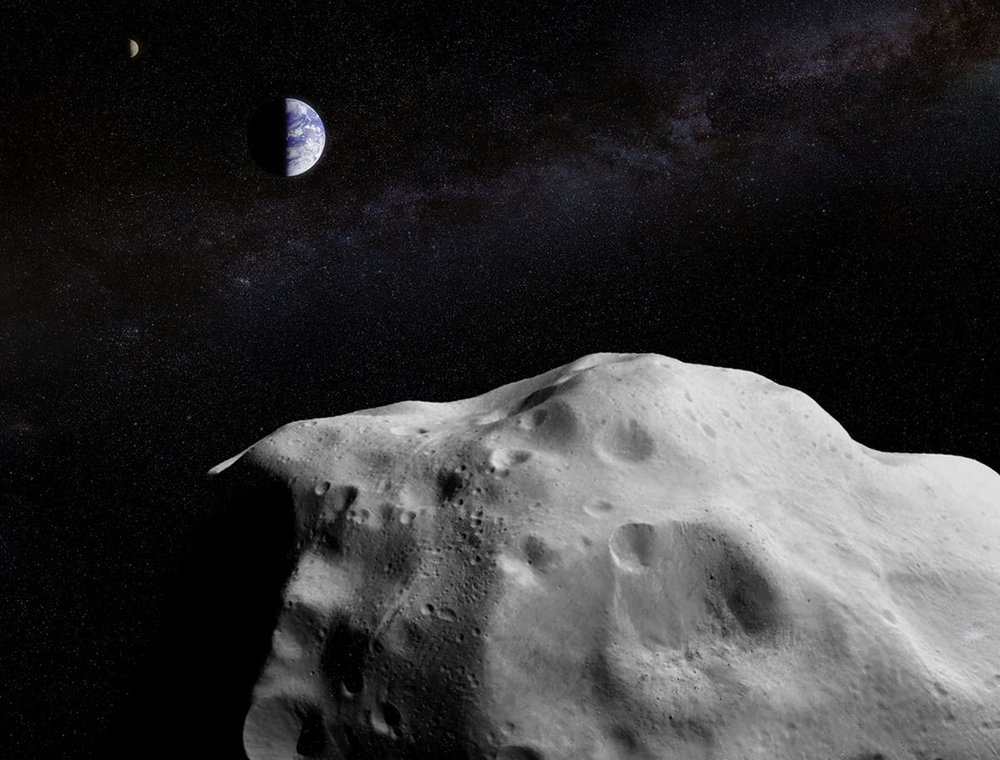 Artist's concept of a large asteroid passing by the Earth-Moon system. - Image Credit: A combination of ESO/NASA images courtesy of Jason Major/Lights in the Dark.