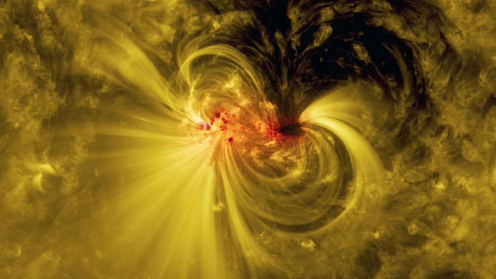 A blended view of the sunspot in visible and extreme ultraviolet light reveals bright coils arcing over the active region — particles spiraling along magnetic field lines. - Image Credit: NASA's Goddard Space Flight Center/SDO