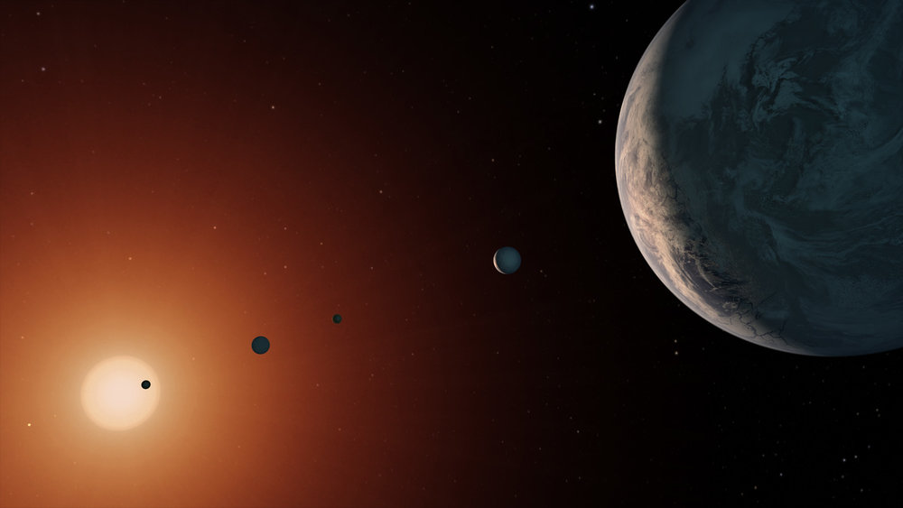 This illustration shows what the TRAPPIST-1 system might look like from a vantage point near planet TRAPPIST-1f (at right). - Image Credits: NASA/JPL-Caltech