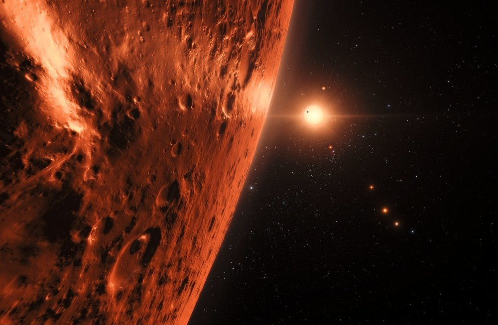 This artist's impression shows the view from the surface of one of the planets in the TRAPPIST-1 system. At least seven planets orbit this ultracool dwarf star 40 light-years from Earth and they are all roughly the same size as the Earth. Several of the planets are at the right distances from their star for liquid water to exist on the surfaces. This artist's impression is based on the known physical parameters of the planets and stars seen, and uses a vast database of objects in the Universe. - Image Credit: NASA/ESA/HST