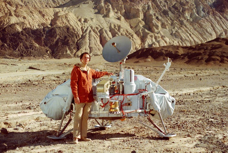 Dr. Carl Sagan poses with a model of the Viking lander in Death Valley, California. - Image Credit: NASA, CC BY