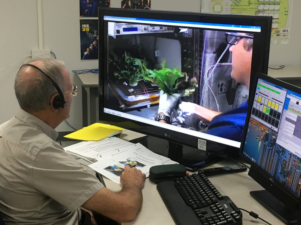 Charles Spern, project manager on the Engineering Services Contract, communicates instructions for the Veggie system to astronaut Joe Acaba on the International Space Station. Spern is in the Experiment Monitoring Room in the Space Station Processing Facility at Kennedy Space Center in Florida. Three different varieties of plants from the Veg-03D plant experiment were harvested. - Image credit: NASA/Amanda Griffin