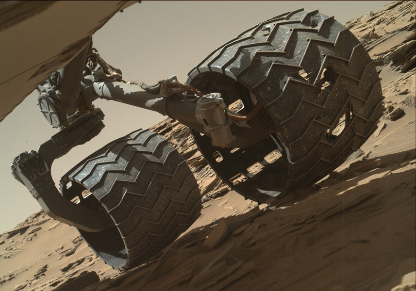 Image taken by the Mars Hand Lens Imager (MAHLI) camera showing the condition of Curiosity's left-middle and left-rear wheels. - Image Credit: NASA/JPL-Caltech/MSSS