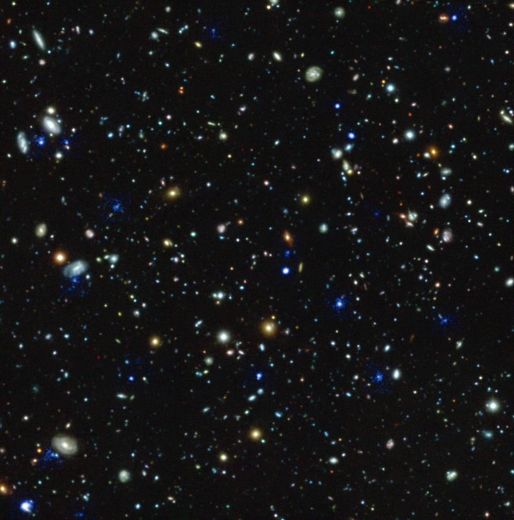 This compound image shows the Hubble Ultra Deep Field region and highlights in blue the glowing haloes of gas around many distant galaxies discovered using the MUSE instrument on ESO's Very Large Telescope in Chile. The discovery of so many huge haloes, which radiate ultraviolet Lyma-alpha radiation, around many distant galaxies is one of the many results coming out of this very deep spectroscopic survey. - Image Credit: ESO/MUSE HUDF team.