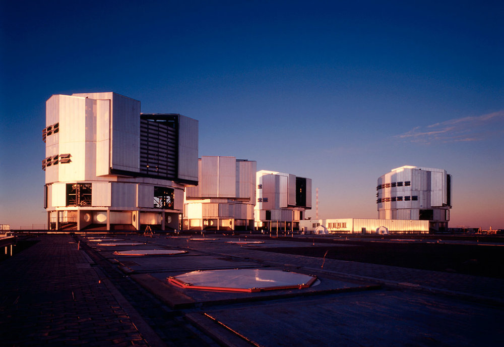 "A view of the upper platform at the ESO Paranal Observatory with the four enclosures for the VLT 8.2-m Unit Telescopes and the partly subterranean Interferometric Laboratory (at centre). YEPUN (UT4) is housed in the enclosure to the right. This photo was obtained in the evening of November 25, 2001, some hours before ""First Light"" was achieved for the new NAOS-CONICA instrument, mounted at that telescope. - Image Credit: ESO"
