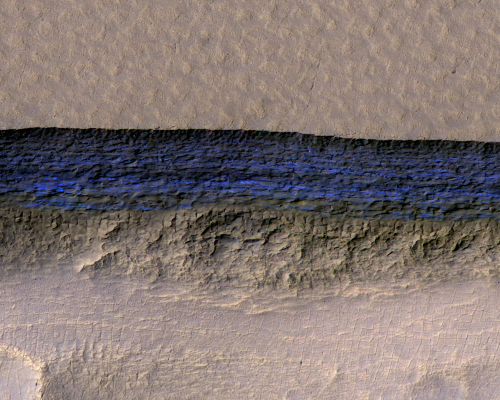 A cross-section of underground ice is exposed at the steep slope that appears bright blue in this enhanced-color view from the HiRISE camera on NASA's Mars Reconnaissance Orbiter. - Image Credits: NASA/JPL-Caltech/UA/USGS