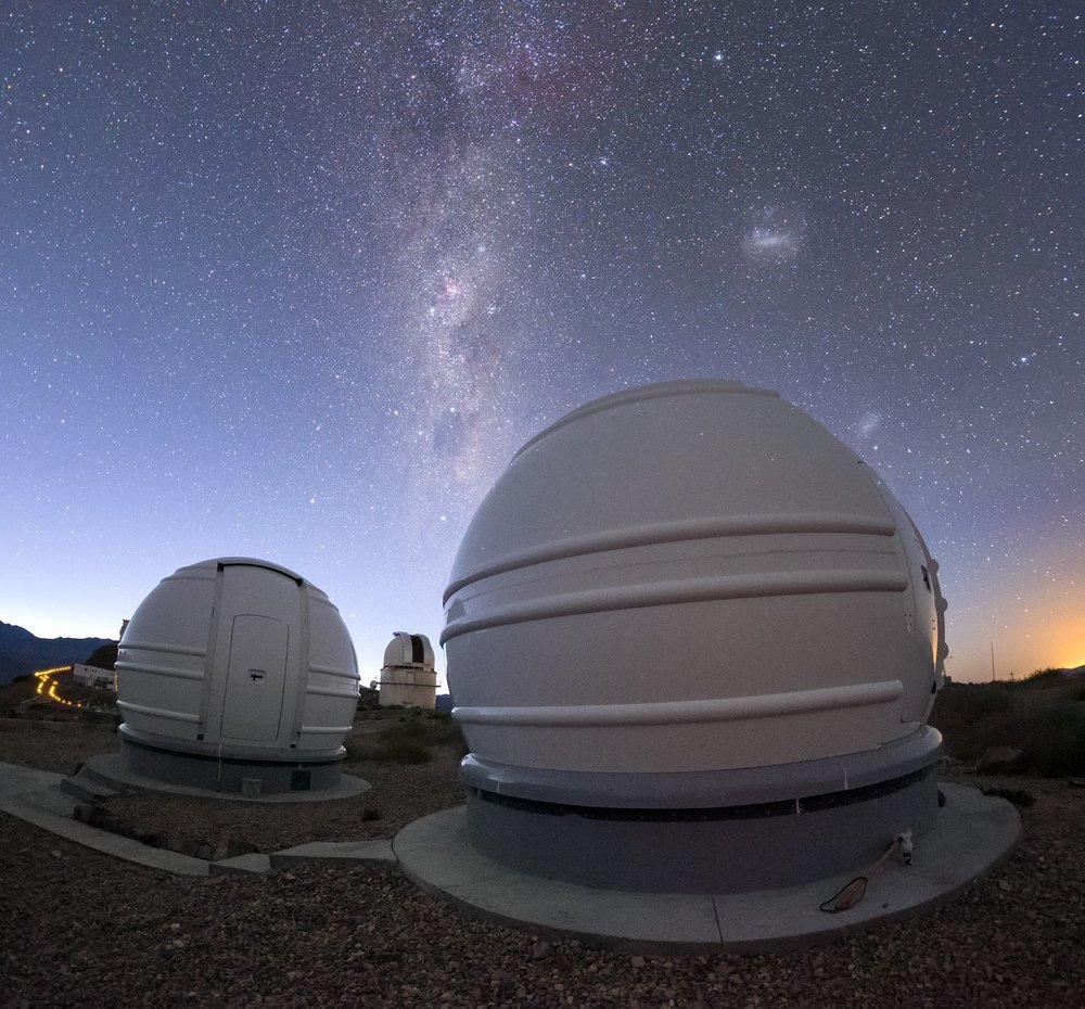 This view shows two of the three ExTrA domes with the Milky Way and Magellanic Clouds visible above.. - Image Credit: ESO/Petr Horálek