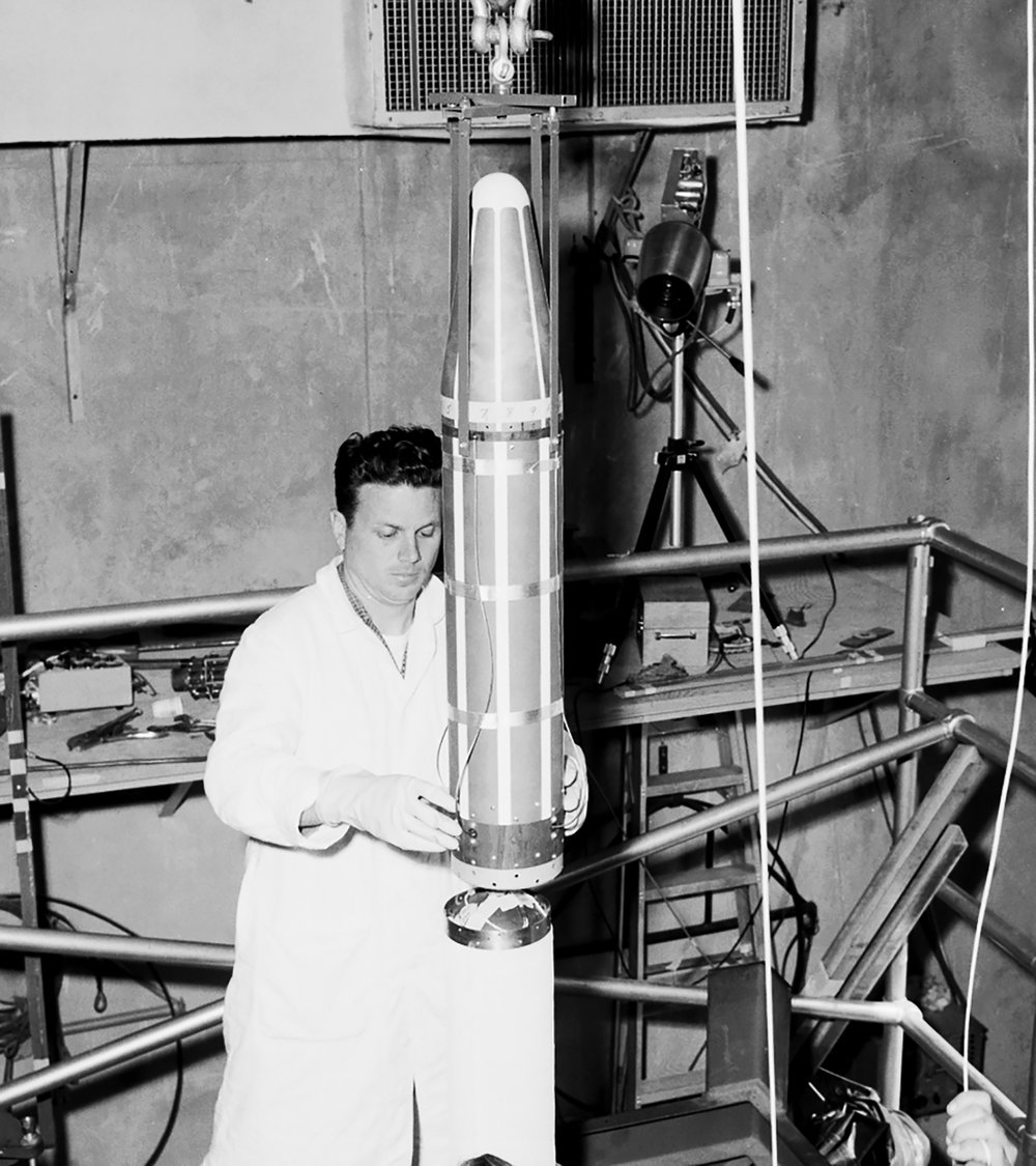 In the gantry at Space Launch Complex 26 at the Cape Canaveral Missile Annex (now Cape Canaveral Air Force Station), a technician lowers the Explorer 1 satellite onto the launch vehicle's fourth stage motor. - Image Credits: NASA (click to enlarge)