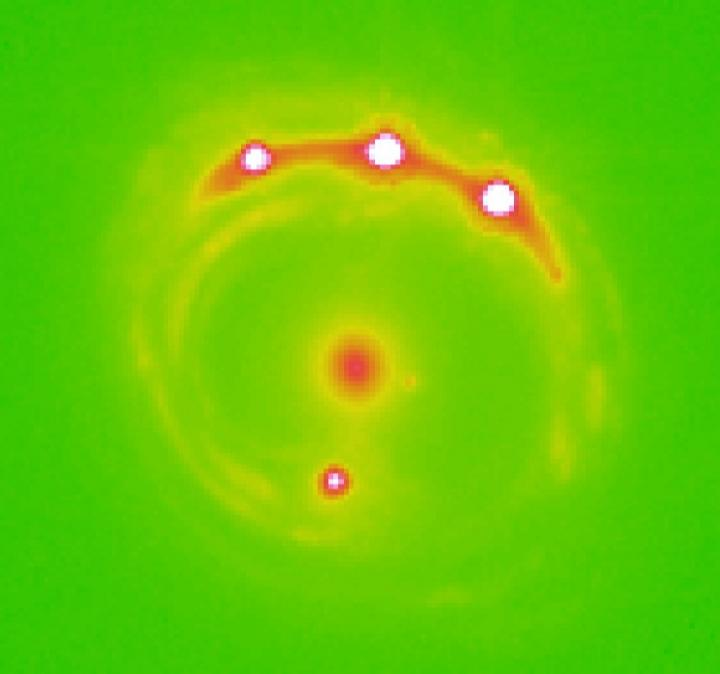 Image of the gravitational lens RX J1131-1231 galaxy with the lens galaxy at the center and four lensed background quasars. It is estimated that there are trillions of planets in the center elliptical galaxy in this image. - Image Credit: University of Oklahoma