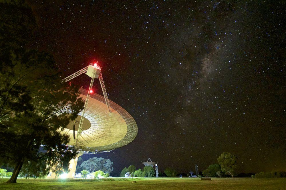 The Parkes observatory is positioned to be isolated from radio frequency interference. The site also sees dark skies in optical light, as seen here in June 2017 with the Milky Way Galaxy overhead. - Image Credit:  Daniel John Reardon via Wikimedia Commons